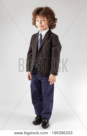 Funny Curly Boy Stands Half-turned, Smiling And Looking At The Camera. Gray Background.