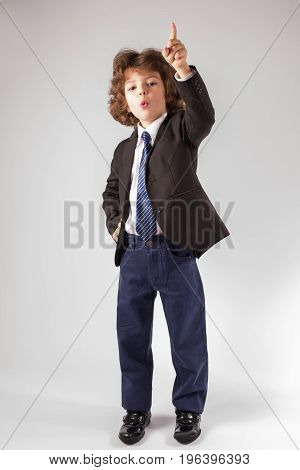 Funny Curly Boy Raised His Hand And Points His Index Finger Upwards. Full Length. Gray Background.