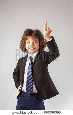 Funny Curly Boy Smiling Raised His Hand And Points His Index Finger Upwards. Full Length. Gray Backg