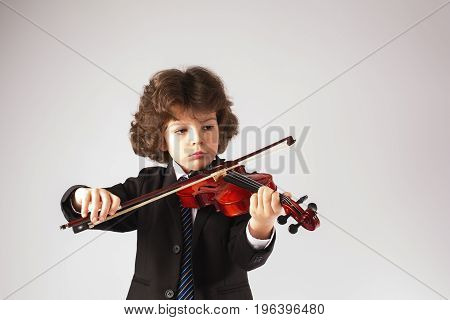 Little Curly Boy Thoughtfully, Playing A Musical Instrument. Gray Background.