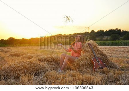 Girl sit down at hay bale at sunset. Young woman enjoy in the countryside