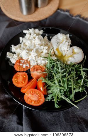 Salad from arugula, tomatoes and poached eggs on a plate