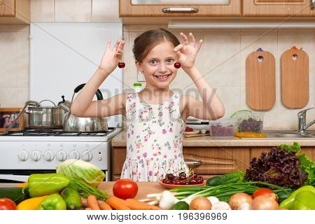 child girl play and having fun with cherries, fruits and vegetables in home kitchen interior, healthy food concept
