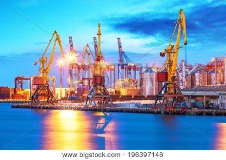 Scenic evening view of the freight sea port with ship cranes and cargo containers