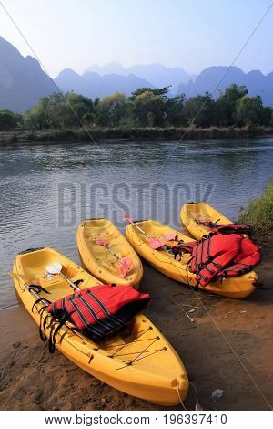 Four yellow canoes with red life vest at riverside beach.