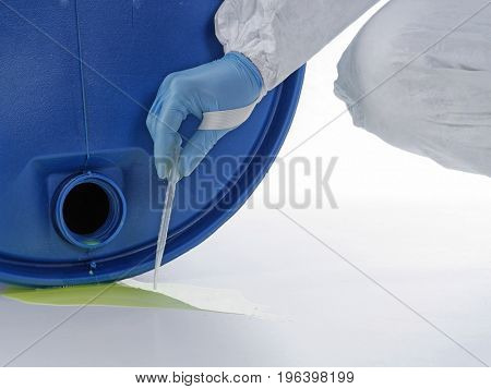 Closeup of man wearing protective suit sampling dangerous chemical liquid leaking from blue container