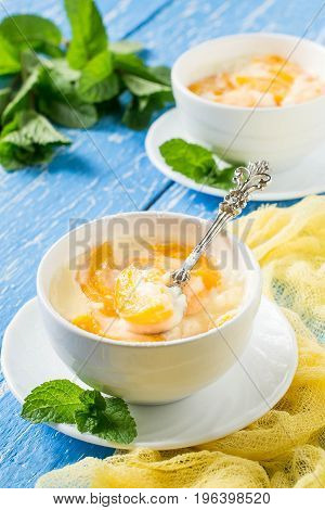 Delicious creamy apricot dessert in white cups on yellow napkin. Summer dessert with fruits. Dietary and healthy food. Vertical