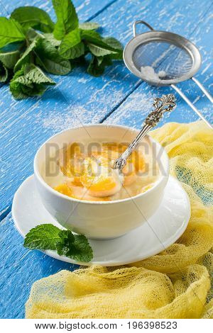 Delicious creamy apricot dessert in white cup on yellow napkin. Sieve with powdered sugar. Summer desserts with fruits. Dietary and healthy food. Vertical