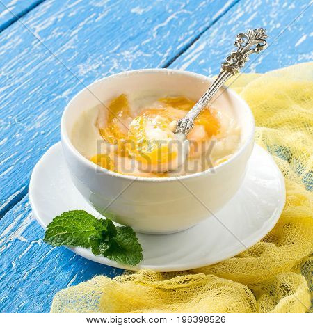 Delicious creamy apricot dessert in white cup on yellow napkin. Summer desserts with fruits. Dietary and healthy food. Square image