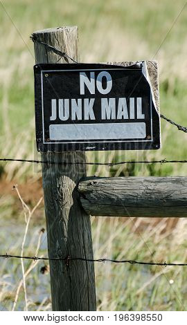 Metal sign on wooden fence warning no junk mail