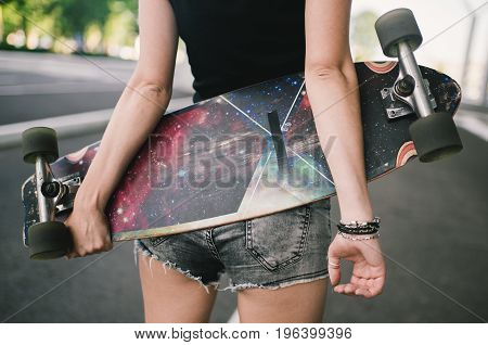 Young caucasian hipster woman with a longboard skateboard on the street