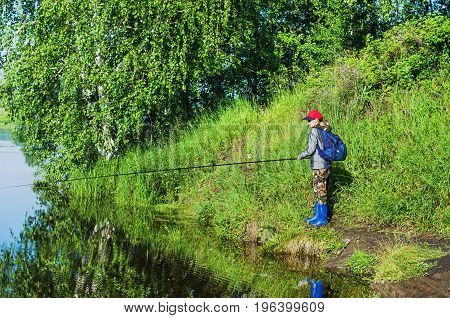 The woman-a fisherman standing with a fishing rod on the Bank of the pond on a summer morning