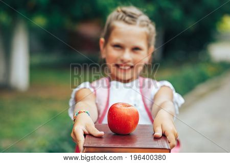 A cute girl is holding a book with a red apple