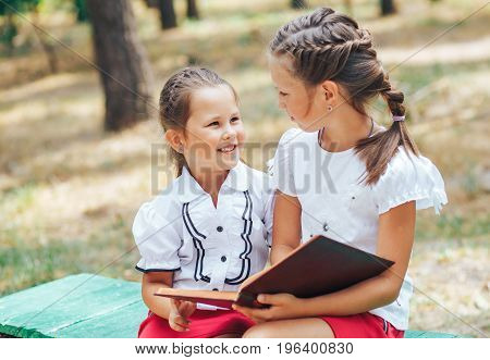The older sister helps to teach the lesson after school. Children are sitting on a bench with a book