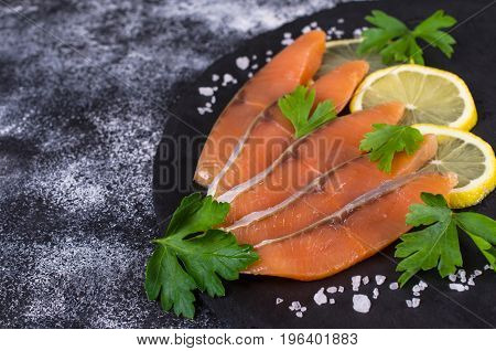 Sliced salted salmon with lemon and parsley. Selective focus.
