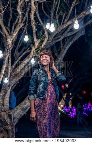 Woman among decorative outdoor string lights hanging on tree in the park at night time. Bali island.