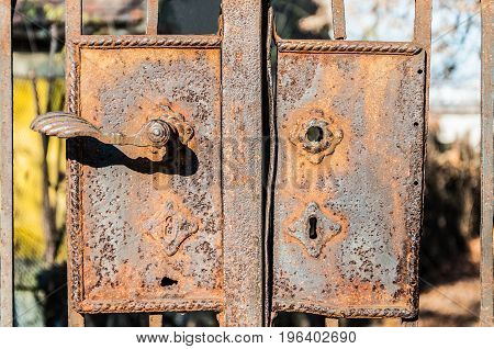 Aged rusty iron gate lock and handle detail. Iron background. Close up.