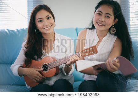 Two Women Are Having Fun Playing Ukulele And Smiling At Home For Relax Time