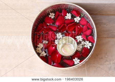 Water with rose petal and jasmine in silver bowl.