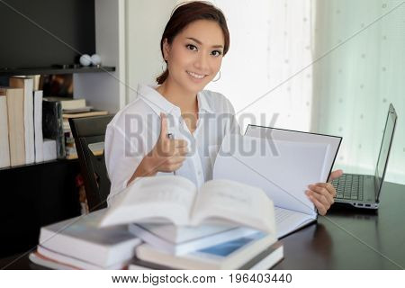 Asian Women Student Smiling And Thump Up Hand Sign And Reading A Book For Relaxation And Final Exam