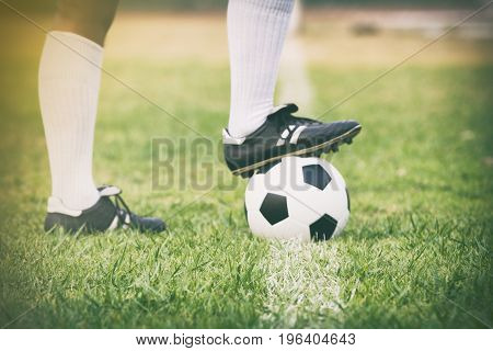 soccer or football player standing with ball on the field for Kick the soccer ball soft focus and selective focus on grass