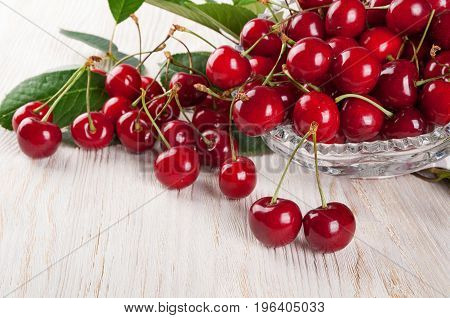 Scattered red sweet cherry and green leaves on a wooden background