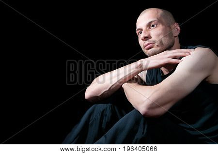 Depressed miserable young man thinking about life. Dark image. Dark background.