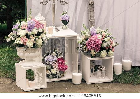 Wedding ceremony decorations bouquets of flowers eustoma, candles in restaurant outdoors.