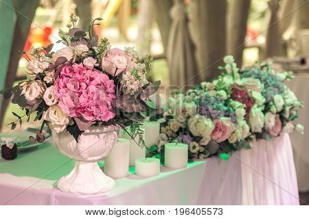 Bouquets of roses and eustoma and candles on decorated wedding table in rastuurant.