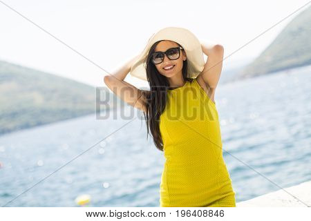 Young Attractive Woman In A Yellow Dress Relaxing By The Sea