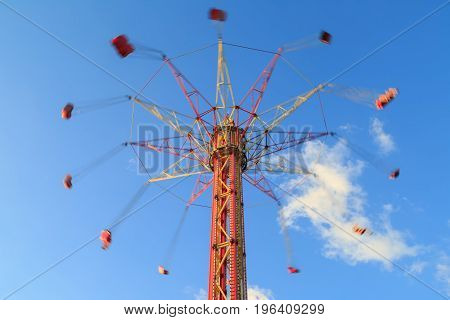 High carousel is whirling on the background of blue sky