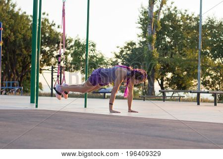 Beautiful fit woman in pink and purple sportwear training on outdoor gym in morning, exercises with suspension straps in park