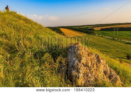 The woman the tourist considers from the hill an agricultural landscape with the processed fields.
