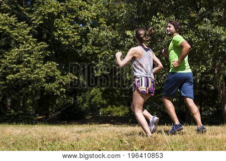 Young Couple Running In The Park On A Sunny Day