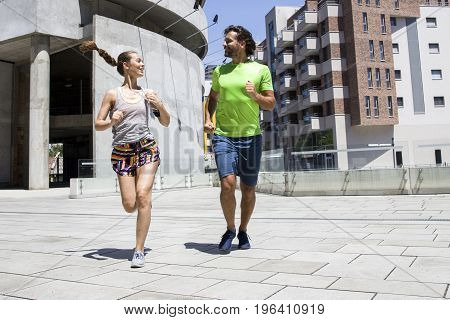 Handsome Man And Beautiful Woman Jogging Together On Street Between Residential Buildings