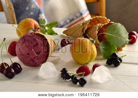 Berry ice cream in waffle cones with fresh berries