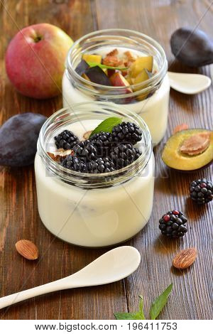 Homemade yogurt in small jars with berries fruits almonds, vertical