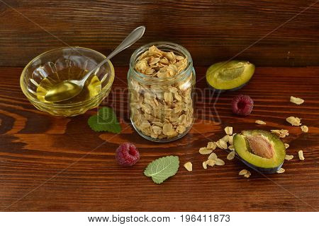 Fresh granola muesli in glass jar yogurt honey plum for healthy breakfast
