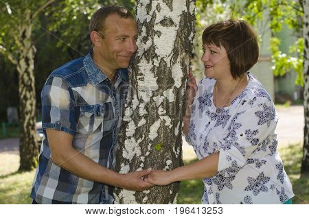 The couple in love clung to the birch tree.