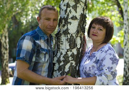 A loving man and woman leaned against the trunk of a birch tree.