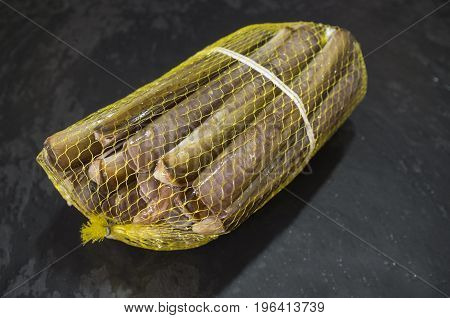 Bundle of razor clams in their plastic net isolated over black slate.