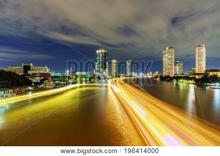 Beautiful cityscape of Bangkok viewing traffic on Chao Phraya river in twilight from Taksin Bridge Thailand