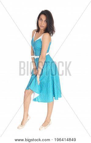 A serious gorgeous young woman standing in full length in a blue dress and holding the dress up isolated for white background.