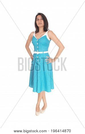 A serious looking gorgeous young woman standing in full length in a blue dress with her hands on her hips isolated for white background.