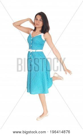 A smiling gorgeous young woman standing in full length in a blue dress on one leg isolated for white background.