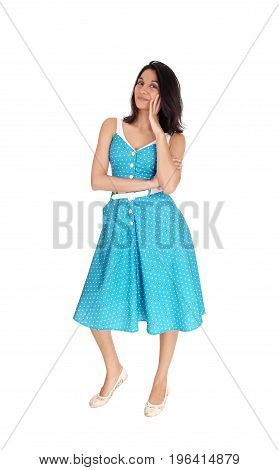A smiling gorgeous young woman standing in full length in a blue dress with one hand on her face isolated for white background.