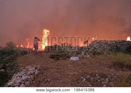 Zrnovnica Split Croatia - July 17 2017: Man fighting with the massive wildfire burning down the forest and villages around city Split