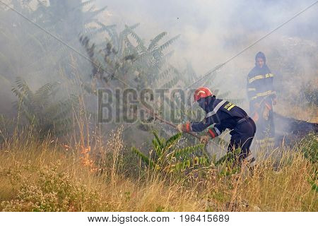 Zrnovnica Split Croatia - July 17 2017: Firefighters gasing the fire with the branches when they run out of water during the massive wildfire burning down the forest and villages around city Split