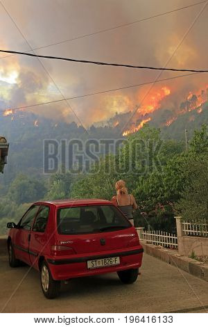 Zrnovnica Split Croatia - July 17 2017: MWoman looking at massive wildfire burning down the forest and villages around city Split
