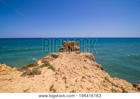 Man Walking And Enjoy The View Of Atlantic Ocean At The Beach With Rocks And Cliffs At The Algarve P